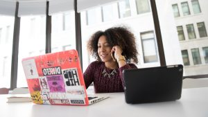 Woman of color on a laptop and phone