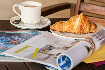 Magazine, croissant, and coffee