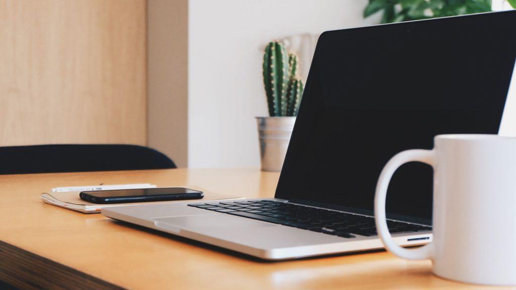 MacBook, coffee mug, and cactus