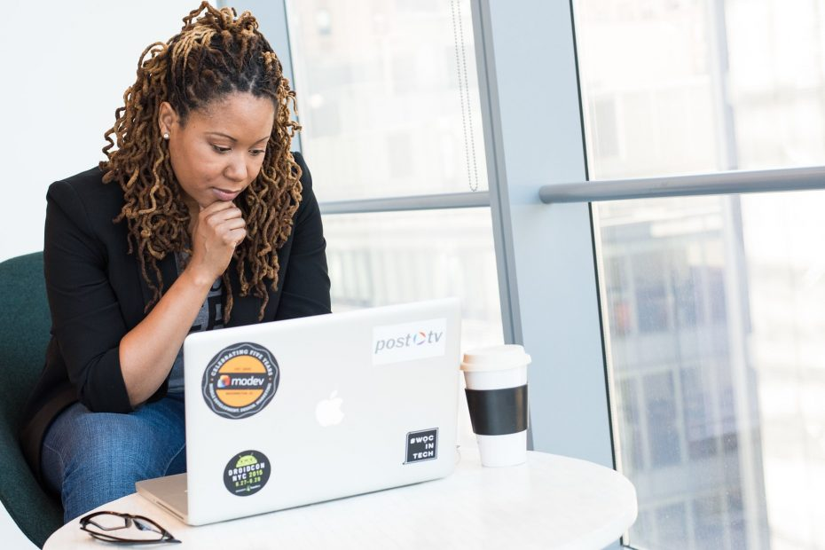 Black woman on MacBook with coffee